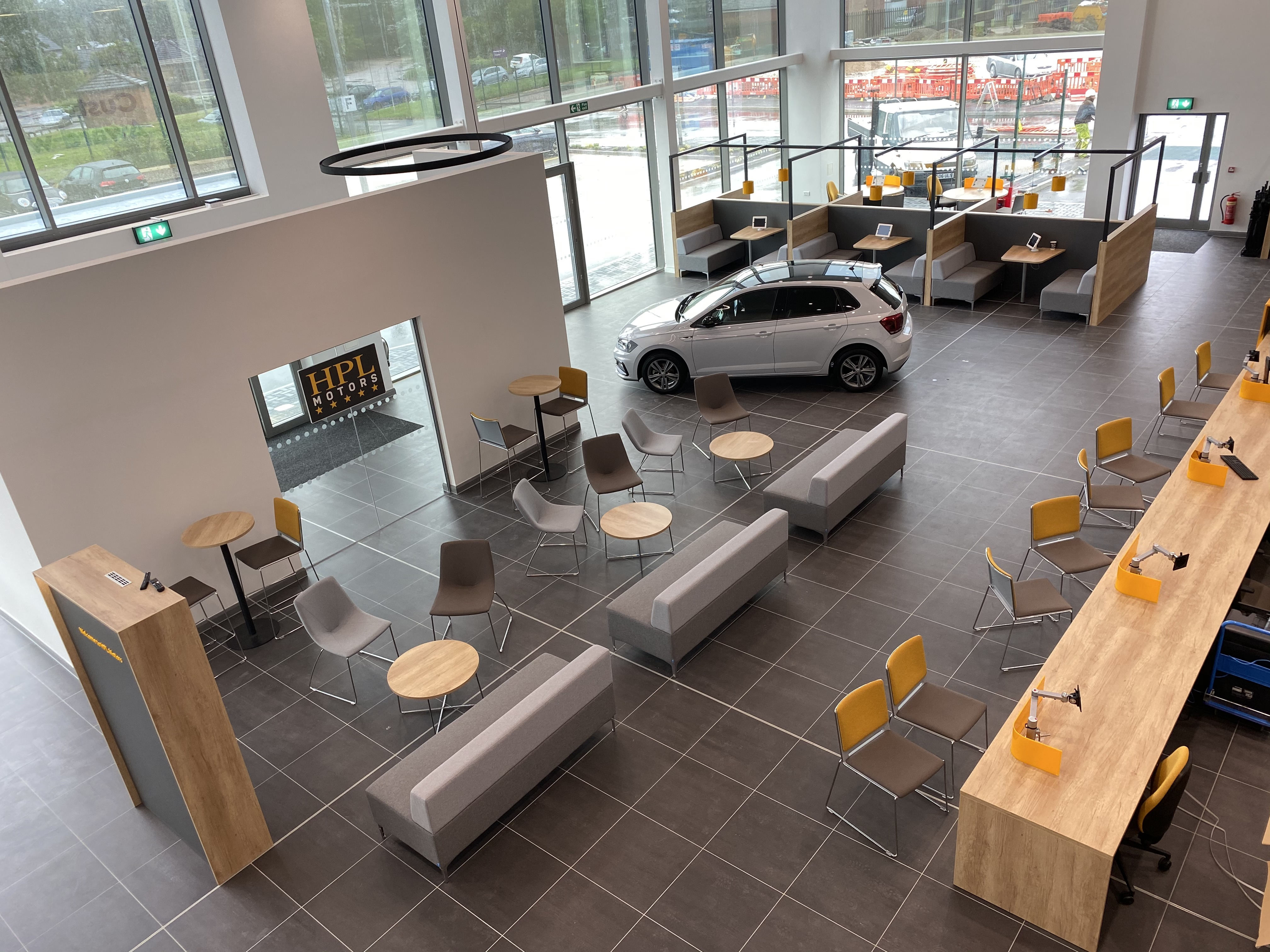 Interior of a HPL Motors Car Showroom with a Car and seating areas surrounding it