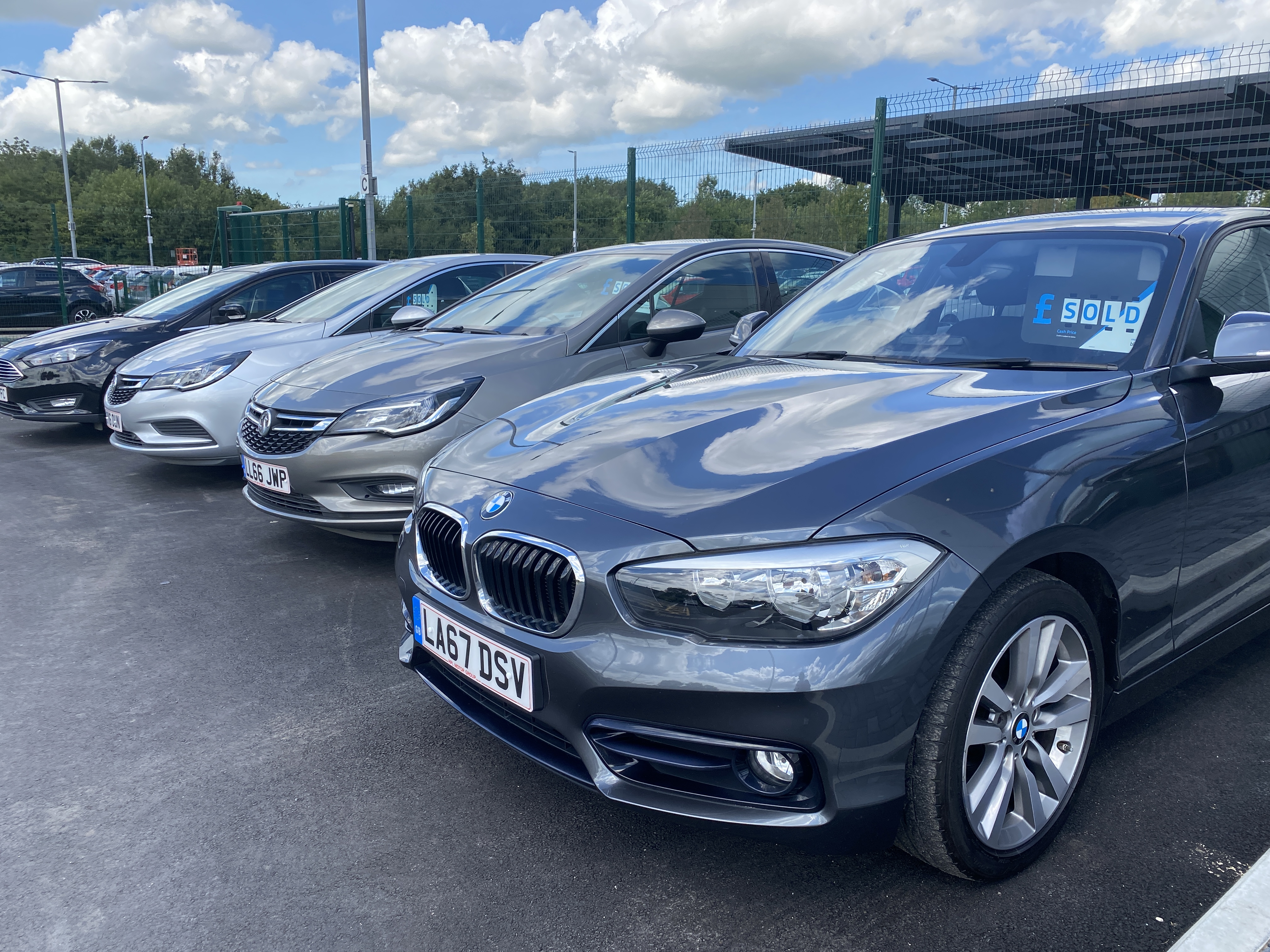 Four cars parked next to each other at a HPL Motors Car Showroom