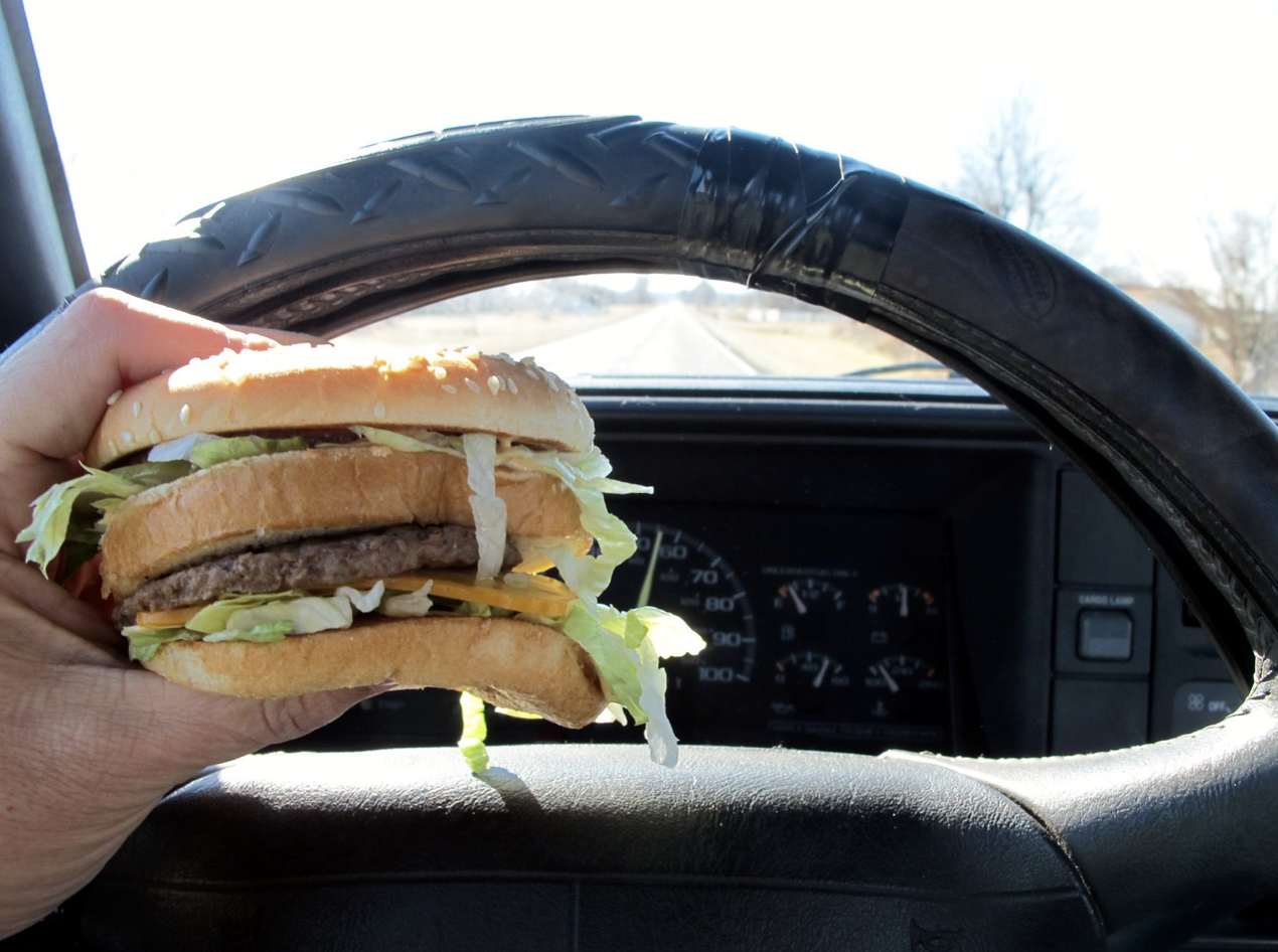 Hand holding a burger at the wheel of a car
