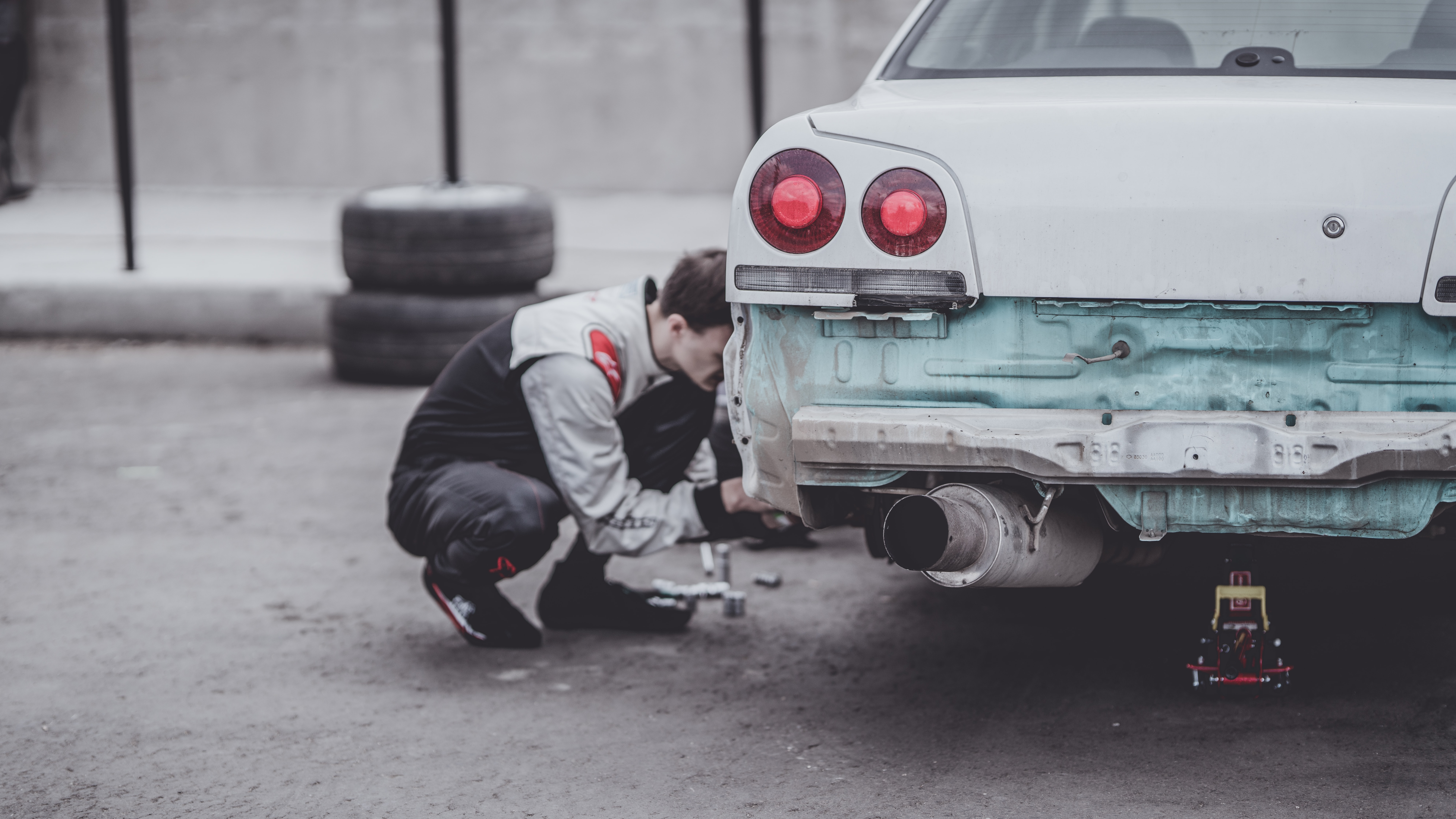 Man bent down to fix an old white car at the rear left hand wheel
