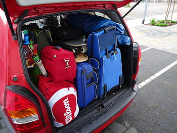 Suitcases packed into the open boot of a red car