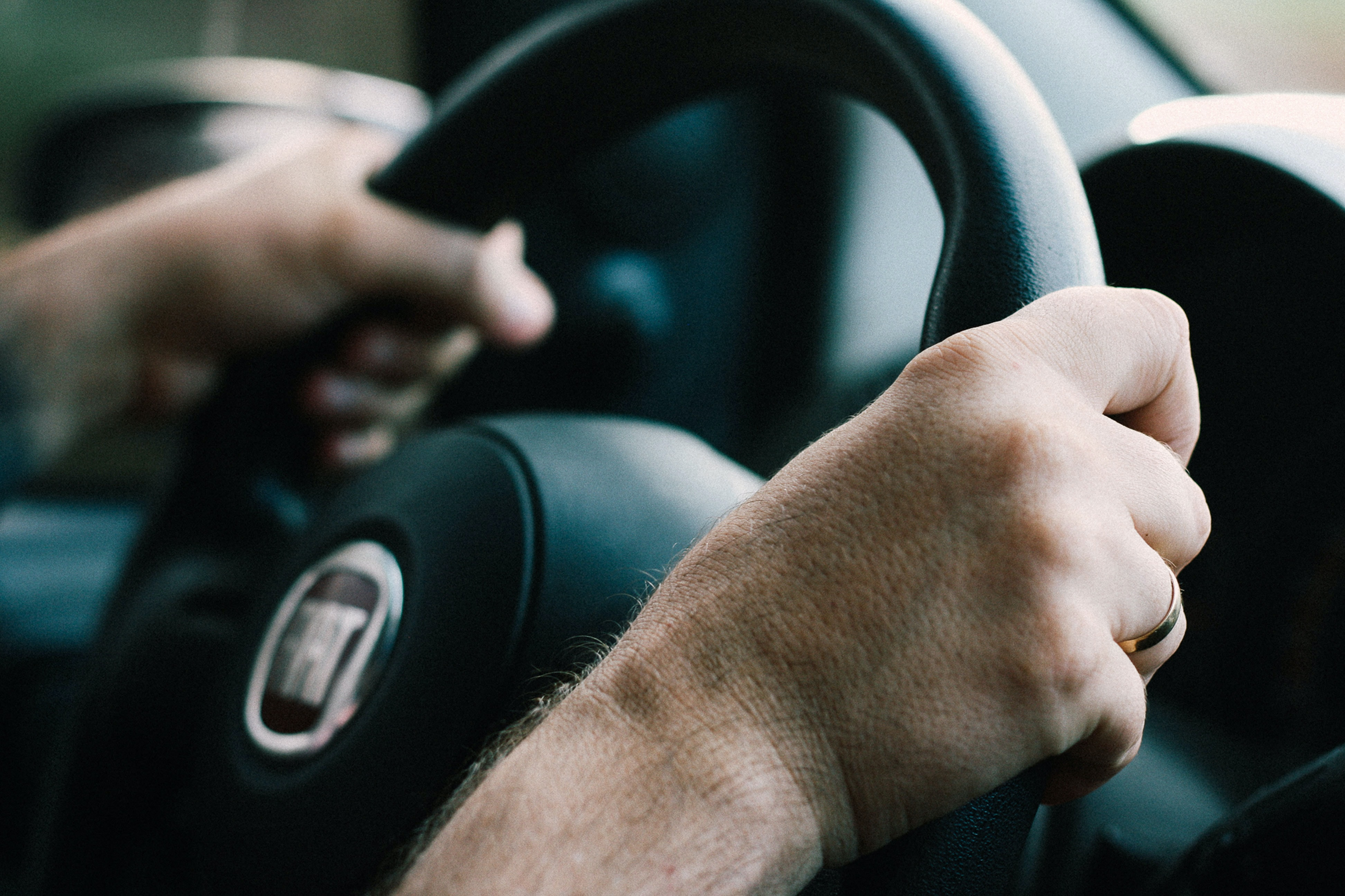 Close up of two hands on the steering wheel of a Fiat 500