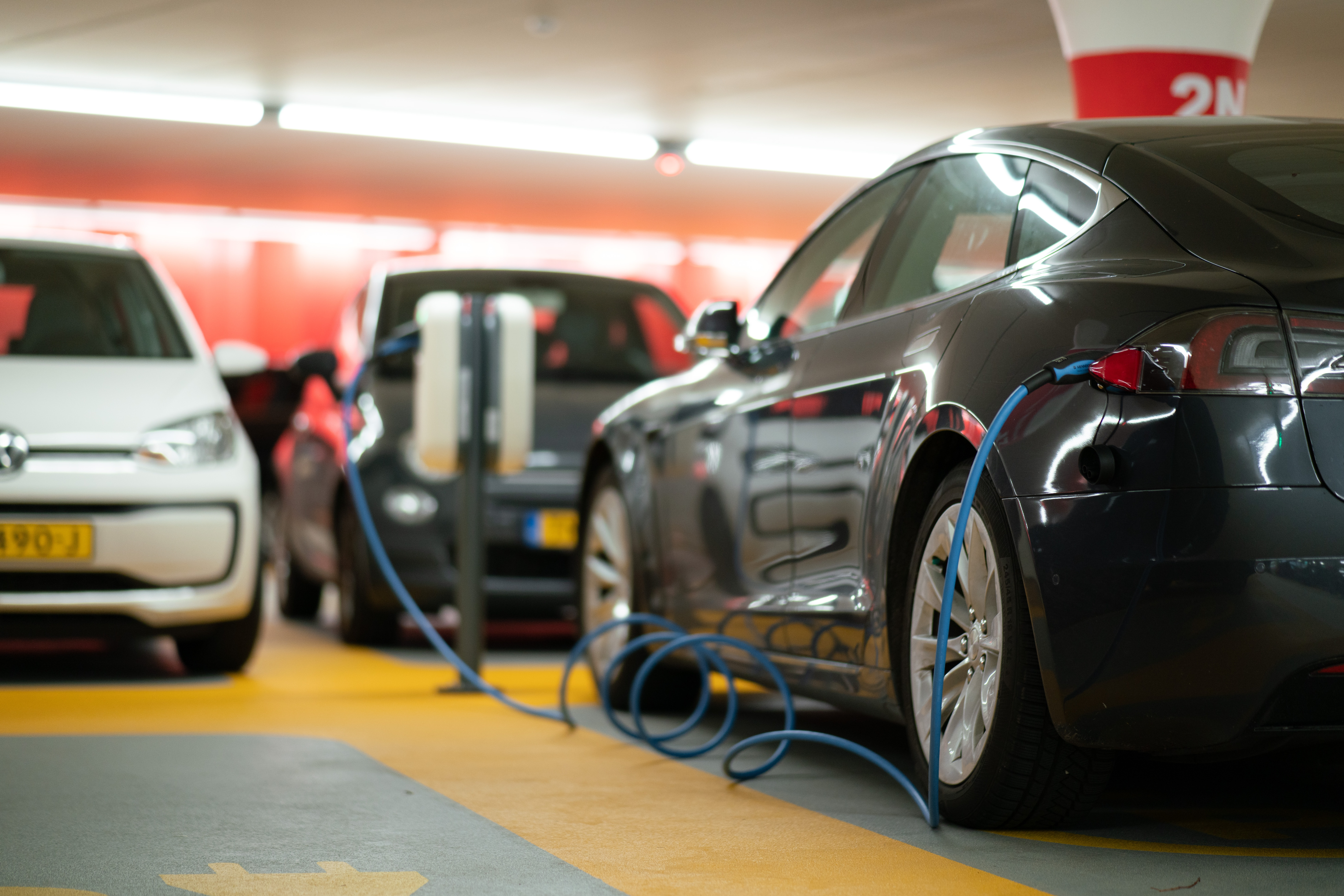 Rear view of a black electric car charging in a car park with a blue cable