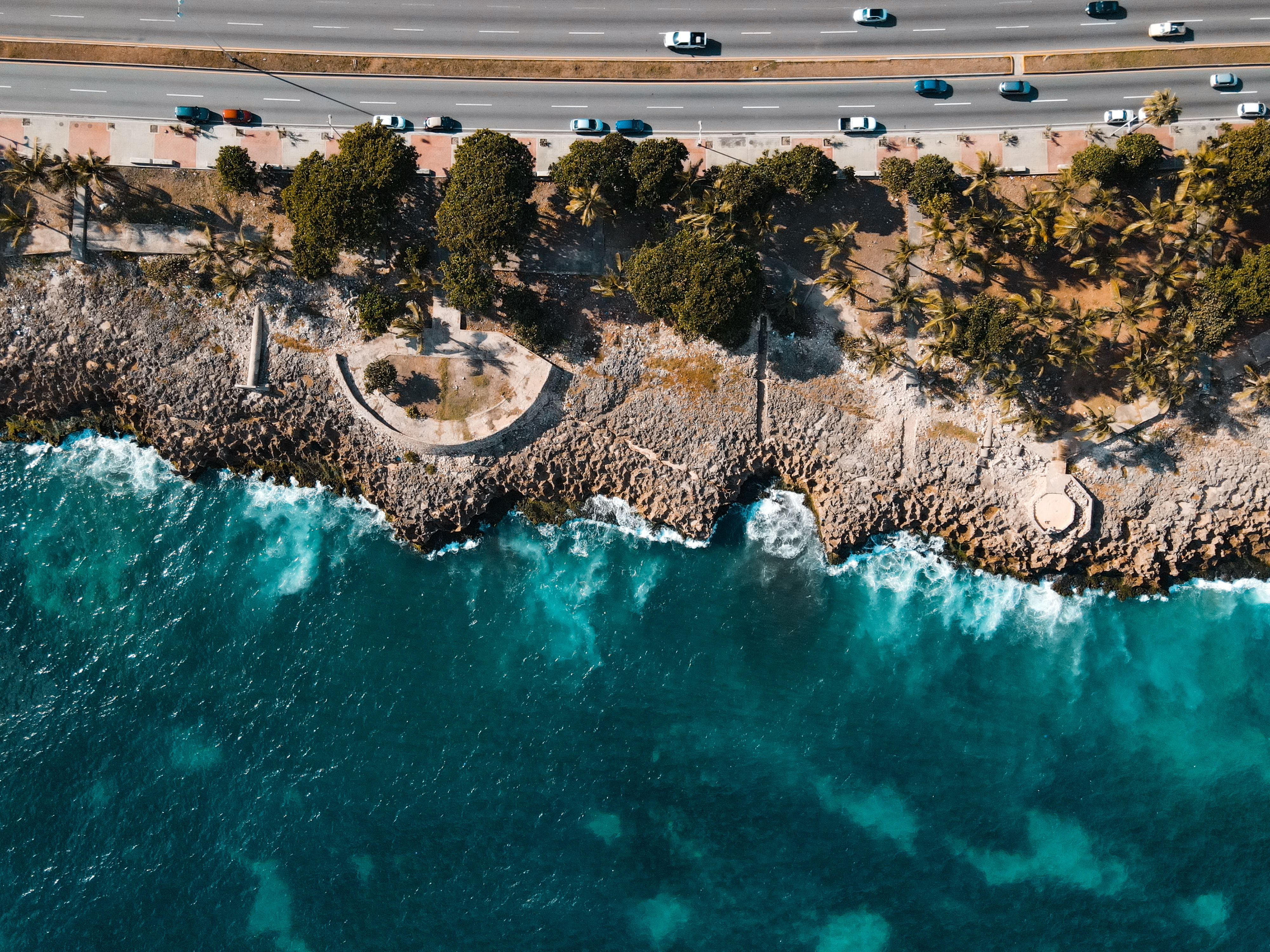 Aerial view of a coastline with a busy road going along side it
