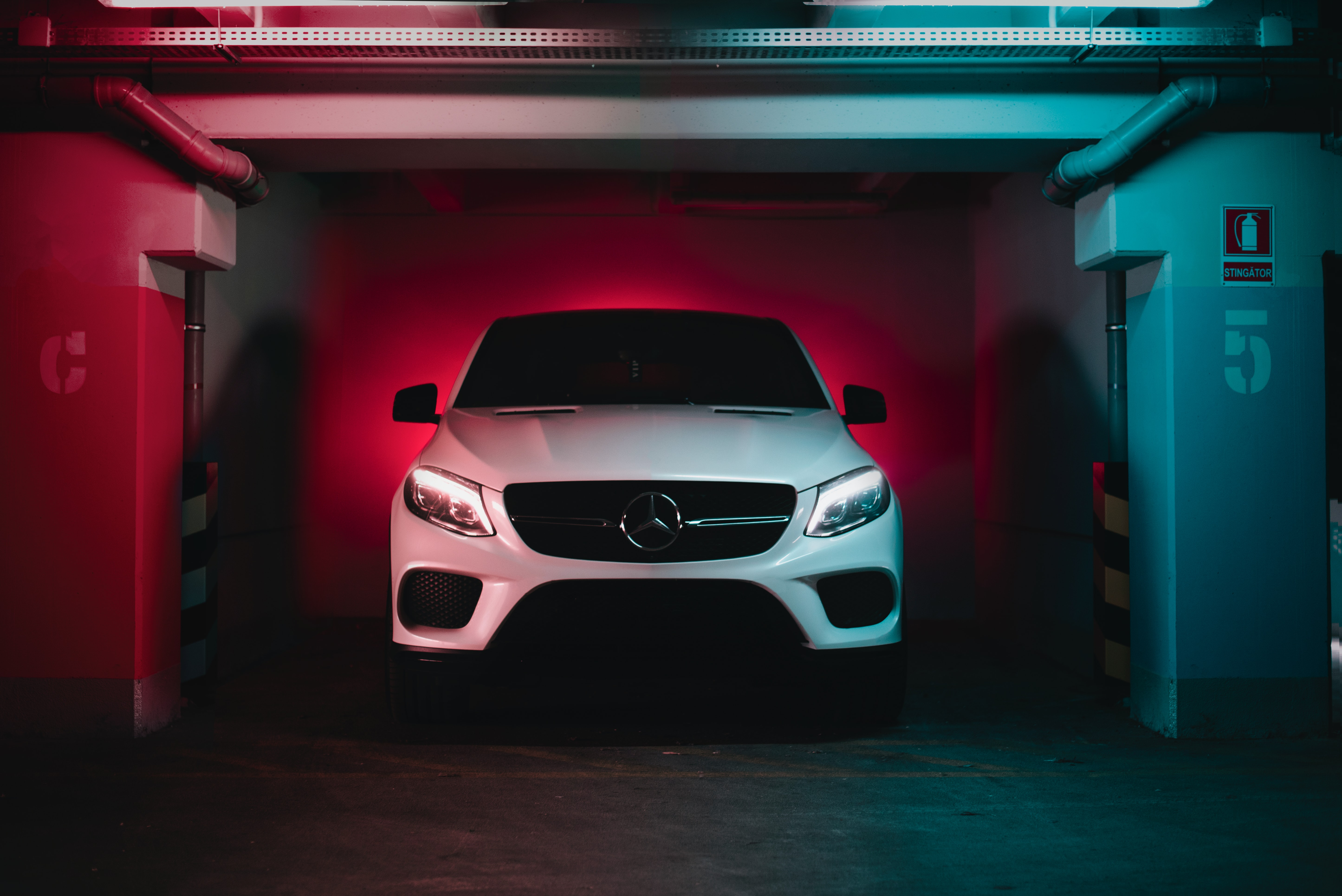 White car in an indoor car park with tail lights on making it glow red