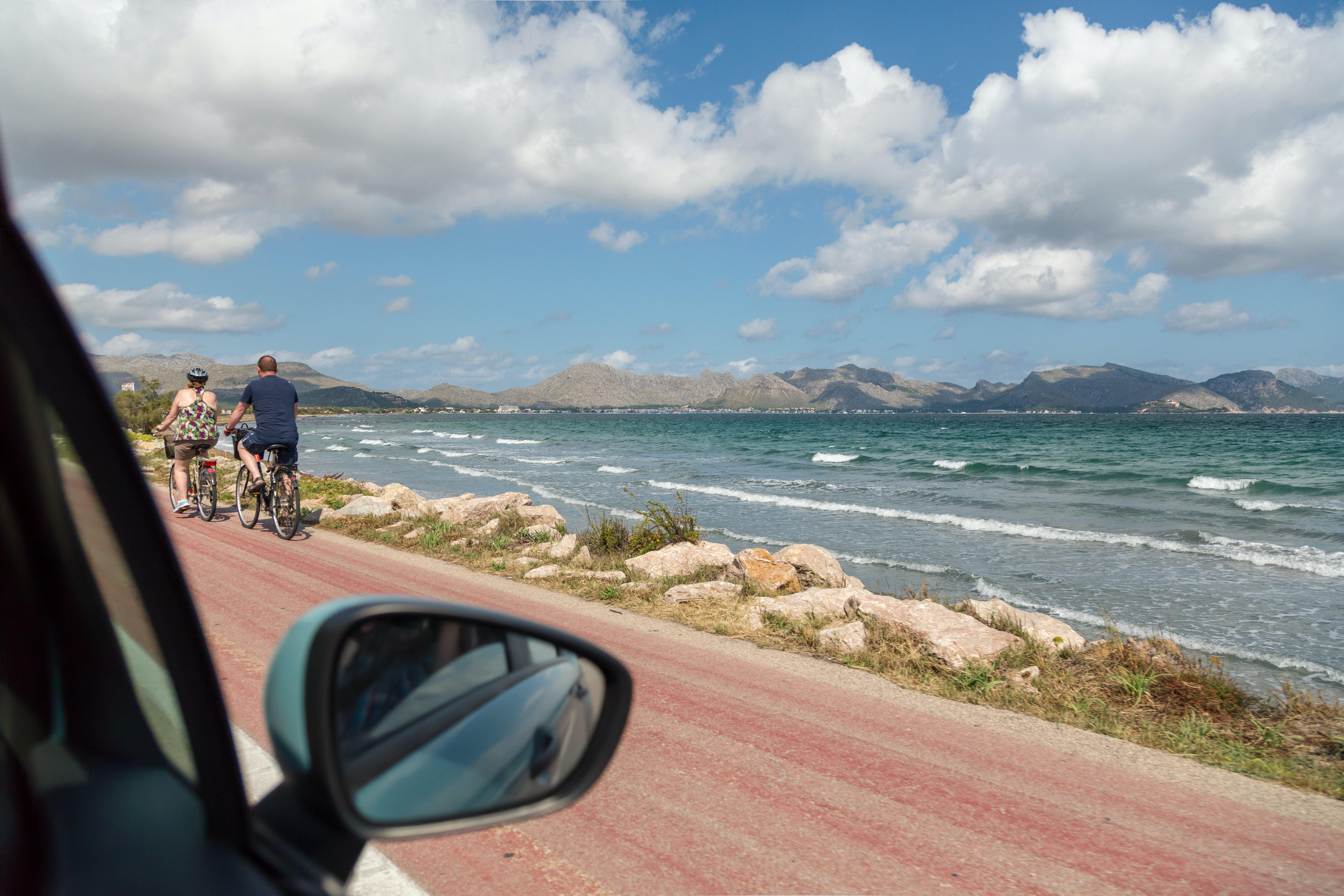 Wing mirror of a car looking out on to the sea with two cyclists riding past